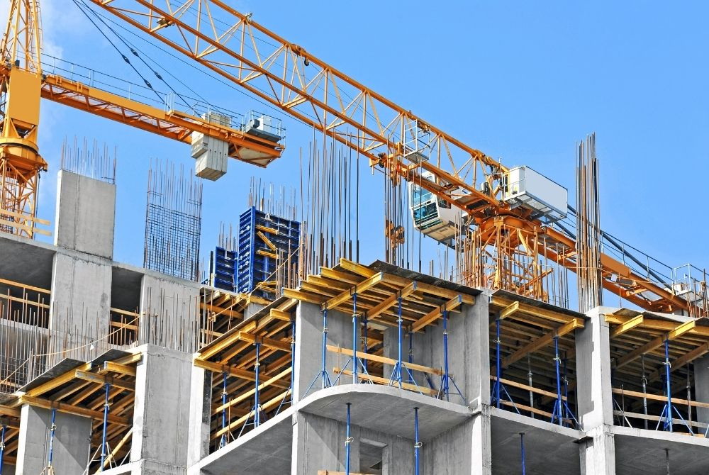 The top of a building site, featuring cranes and concrete